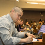 Student veterans takes notes in class