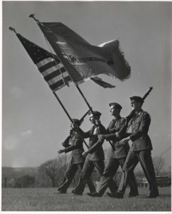 Vintage photo of military students walking with flags