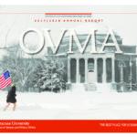 ROTC cadet running through SU quad in the snow holding USA flag.