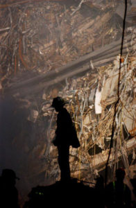 fireman standing with wreckage from 9/11 behind him.