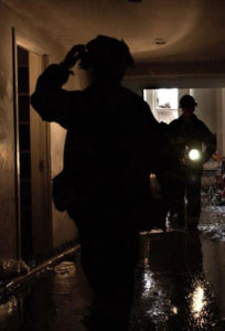 fireman walking through flooded hallway.