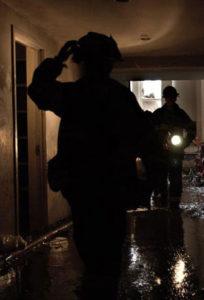 fireman walking through flooded hallway.