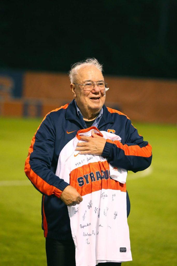 Alejandro Gracia holding autographed SU Soccer Jersey.