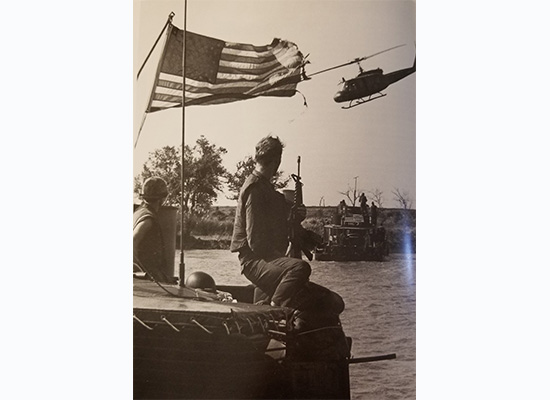 US Navy sailor looking at flag with helicopter flying by
