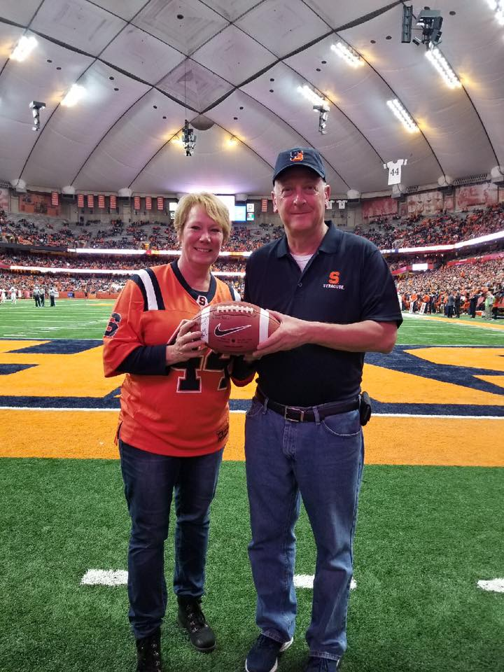 Peggy Combs and her husband posing with football on SU Dome turf.
