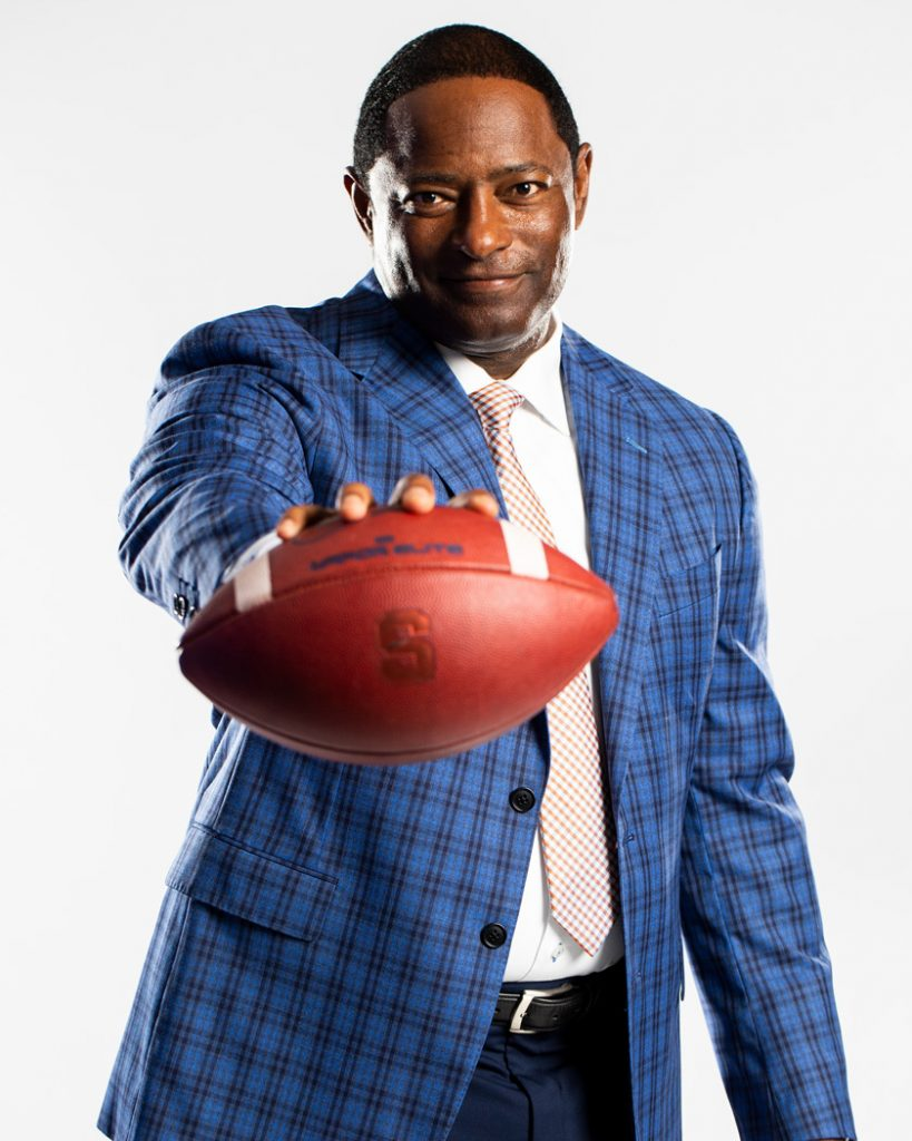 Dino babers holding football.