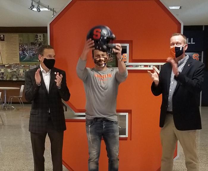 Jay Knight holding up SU football helmet.