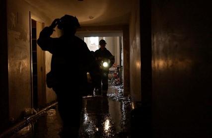 Firemen in dark hallway