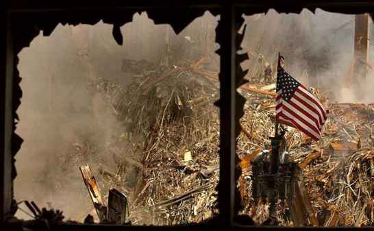 Firemen in rubble with flag.